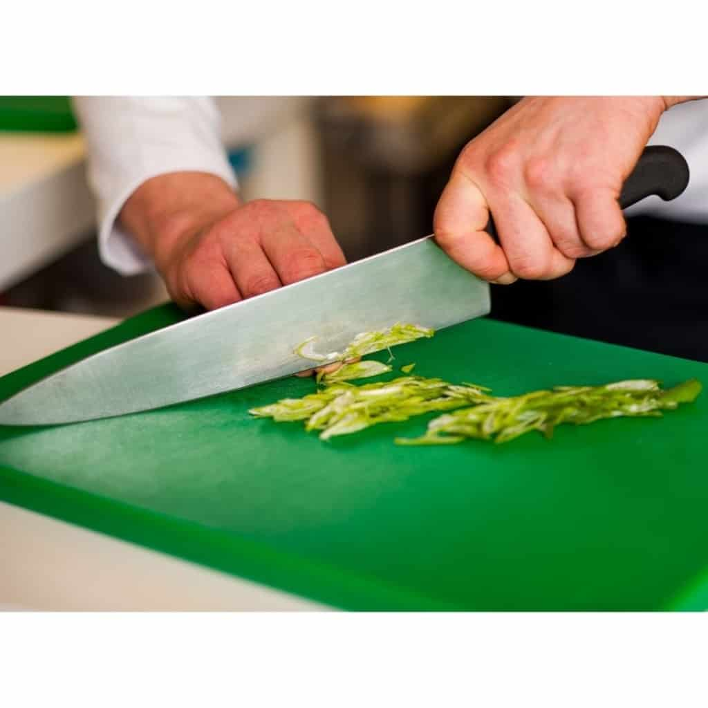 Chef slicing asparagus on a green chopping board